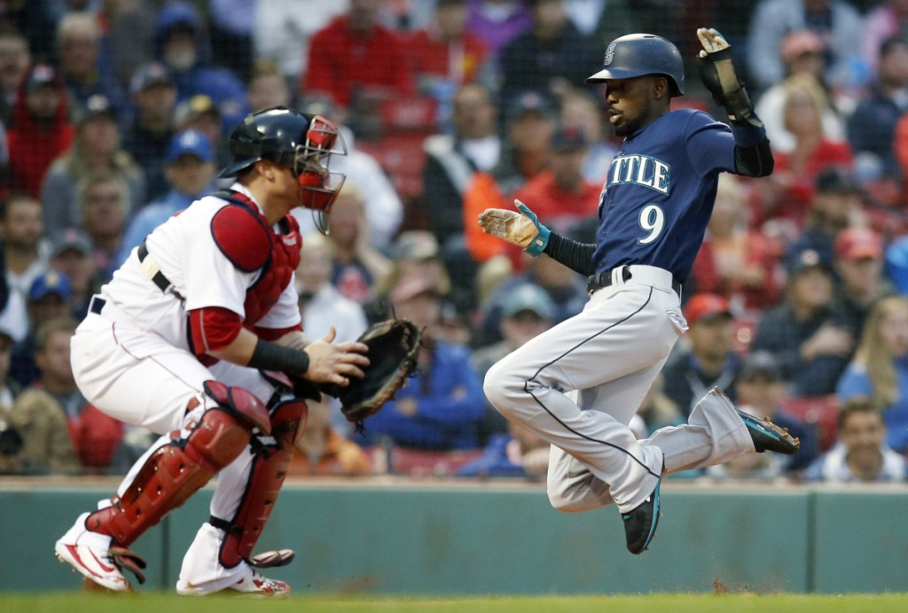 Seattle's Dee Gordon scores on a double by Mitch Haniger as Red Sox catcher Christian Vazquez waits for the throw in the first inning Saturday night at Fenway Park. Haniger drove in three runs in a 7-2 victory.