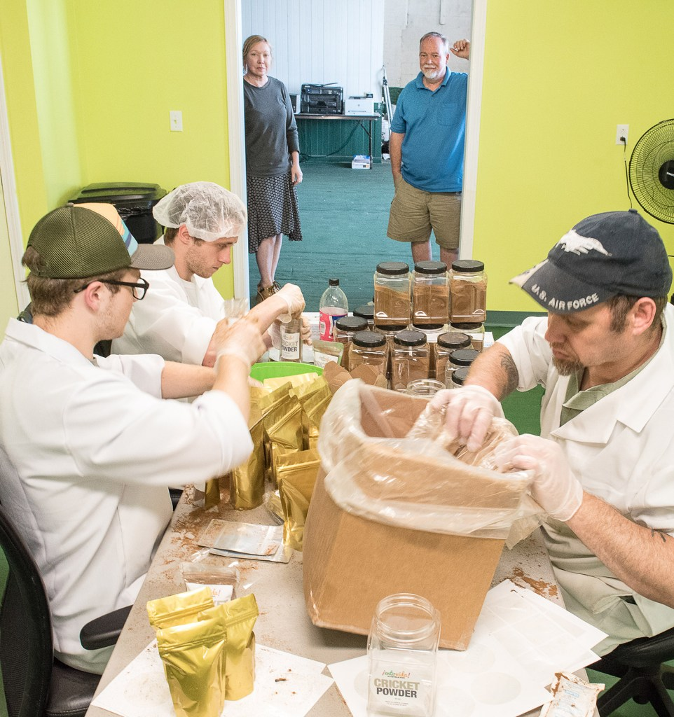 Sister and brother Susan and Bill Broadbent, background, watch employees package cricket powder at their business, Entosense LLC, at the Hill Mill in Lewiston on Tuesday.