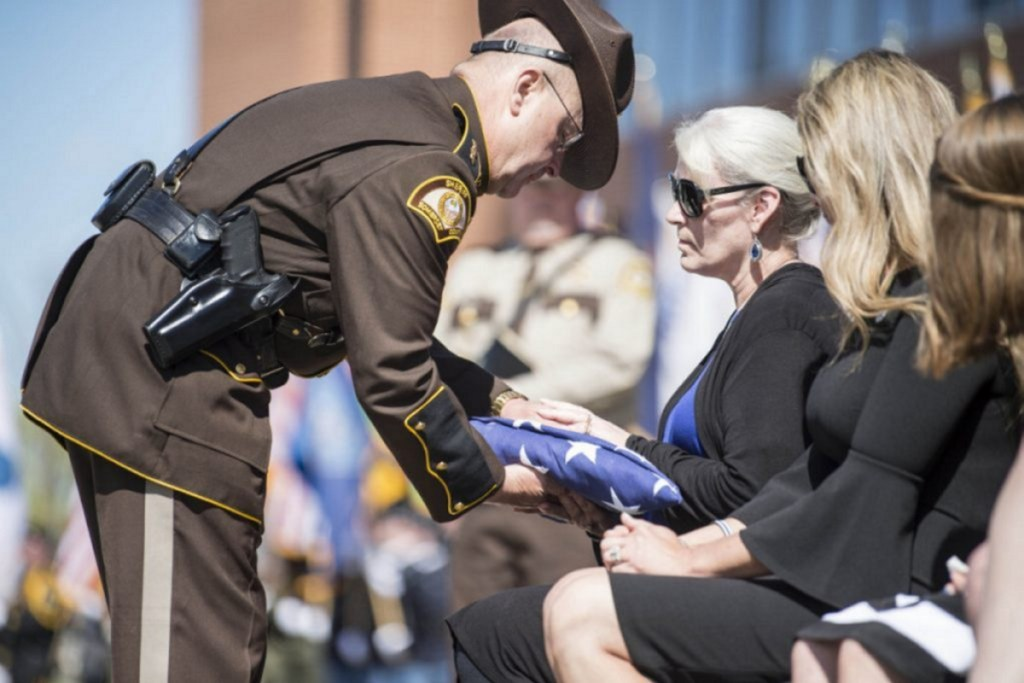 Somerset County Sheriff Dale Lancaster offers a folded American flag to Sheryl Cole, widow of Cpl. Eugene Cole, on May 7 during Cpl. Col's funeral at the Cross Insurance Center in Bangor.