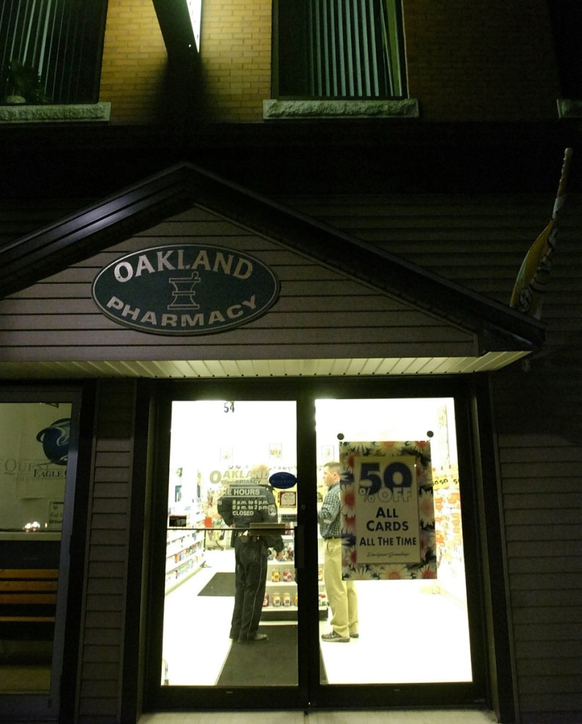 A police officer talks to an individual inside The Oakland Pharmacy on Main Street as part of the investigation of a robbery that occurred there on Oct. 31, 2007.