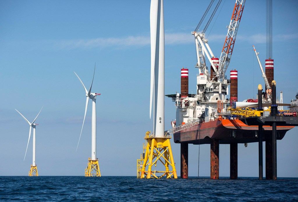 In this Aug. 15, 2016 file photo, A lift boat, right, that serves as a work platform, assembles a wind turbine off Block Island, R.I., in 2016. Officials in Massachusetts announced in May that Danish energy investor Copenhagen Infrastructure Partners and Avangrid Renewables, part of the Spanish company that owns Central Maine Power, had been selected to build the country's first large-scale offshore wind project off Martha's Vineyard.