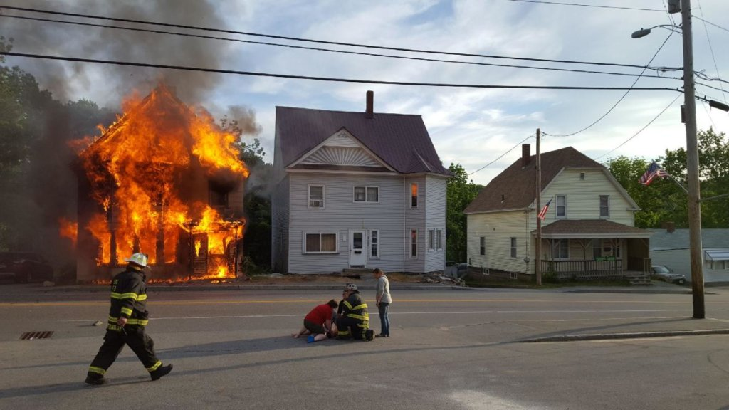 People tend to a child who escaped a burning house Tuesday night on Main Street/Route 4 in Livermore Falls. The child was injured when he jumped from a window, witness Warren Forbes of Livermore said.