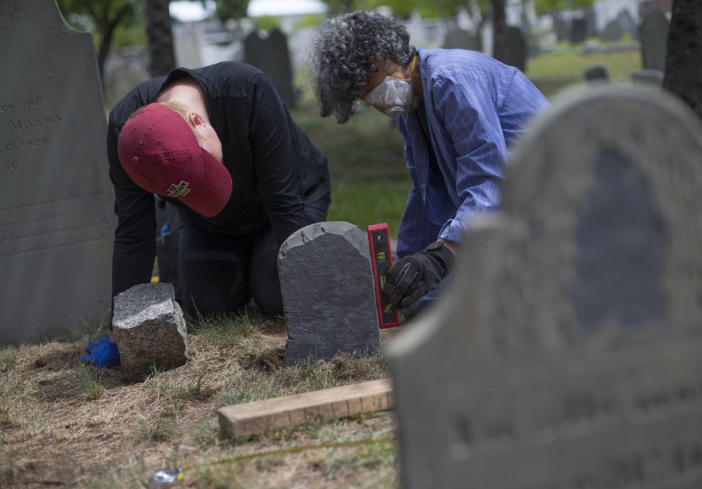 "PORTLAND, ME - JULY 14: Eastern Cemetery in Portland is celebrating 350 years. Sarah Whitmore, left, and Diane Brakeley, members of Spirits Alive, a nonprofit group formed 11 years ago to restore and preserve the cemetery, set a footstone belonging to the grave of George McDowell on Saturday, July 14, 2018, after it was recently recovered near the ""dead house"". (Photo by Derek Davis/Staff Photographer)"
