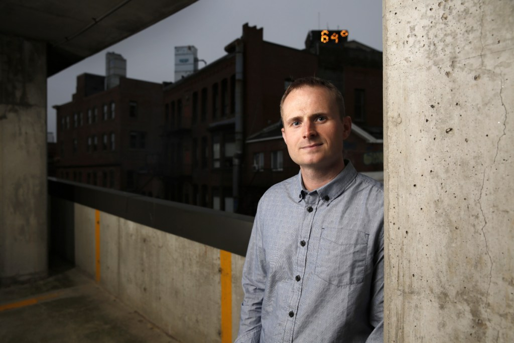 "Michael Koryta poses for a photo in a parking garage in Portland's Monument Square. His latest book, ""How it Happened,"" revolves around two missing bodies, the opioid epidemic in a coastal Maine town and a relentless FBI agent."