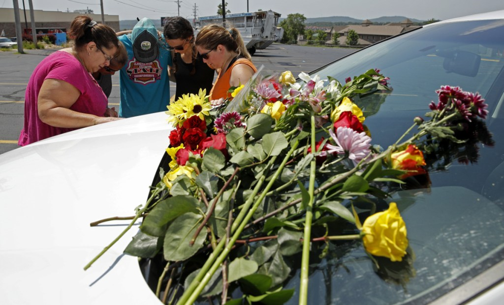 People pray next to a car believed to belong to a victim of Thursday night's duck boat accident in the country-and-western tourist town of Branson, Mo.