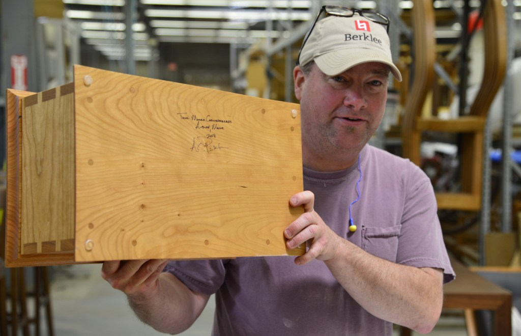 Thos. Moser cabinetmaker Andy Pinkham, who himself is running Saturday's Beach to Beacon 10K, with one of the handcrafted boxes presented to winners.