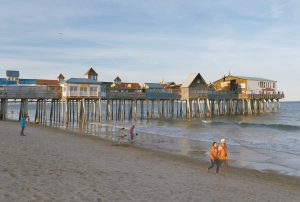 VACATIONING TOURISTS stroll along the edge of the Atlantic Ocean near The Pier in Old Orchard, Beach on June 26. AP PHOTO / ROBERT F. BUKATY