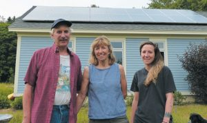 FROM LEFT, Jake Plante, Marcia Harrington and Alexandra Plante stand in front of the solar panels mounted on the garage at their Rossmore Road home in Brunswick. The solar panels are now being assessed by the town and taxed as real property, a decision Plante, Harrington and six other property owners with solar panels are seeking to have overturned by the Brunswick Board of Assessment Review. DARCIE MOORE / THE TIMES RECORD
