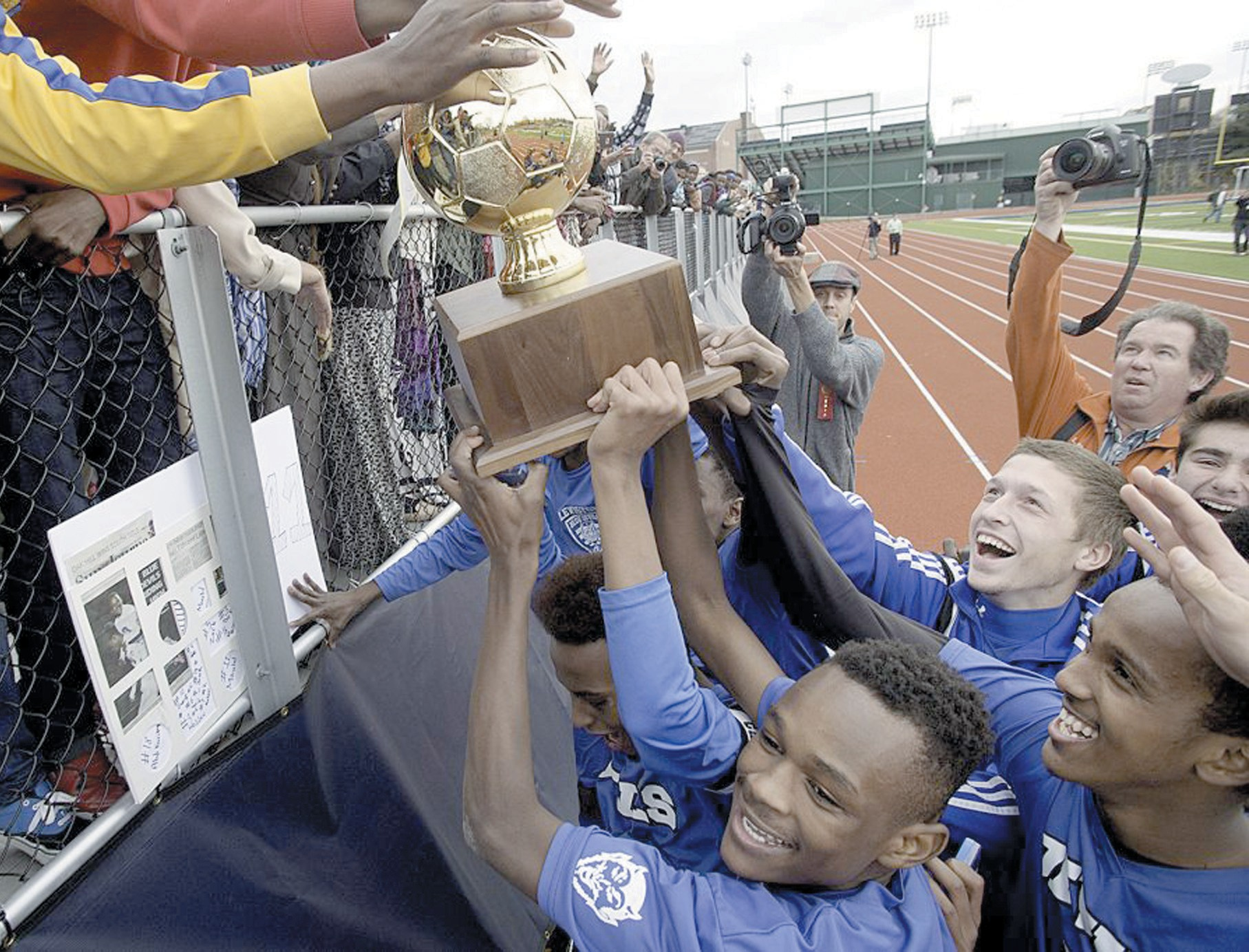 THE LEWISTON HIGH SCHOOL soccer team hoists the Maine Principal's Association trophy for their fans to see after winning the Class A state championship. SUN JOURNAL PHOTO