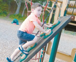FINN KIDNEY, 4, of Waldoboro heads up a climbing wall while playing on the playground at the Topsham recreation fields on Foreside Road Sunday evening. DARCIE MOORE / THE TIMES RECORD