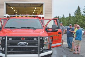 """BOWDOINHAM'S FIREFIGHTERS took time Monday to show off the new quick-attack truck at the completion of the """"wet down"""" ceremony. CHRIS QUATTRUCCI / THE TIMES RECORD"""