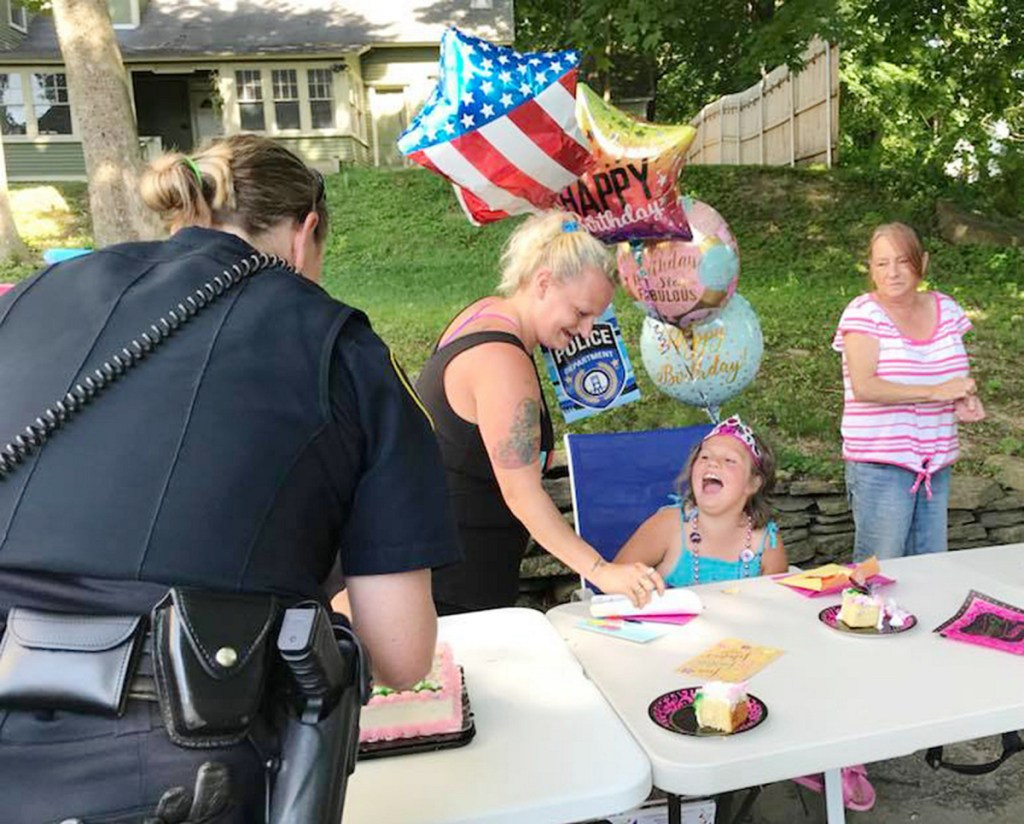 Larriah Binns, 8, of Sidney laughs with Augusta Police Officer Carly Wiggin Sunday at an impromptu birthday party on Murray Street. The celebration was arranged by Augusta police after they learned that none of Larriah's friends came to the party a day earlier. Helping Larriah is her mother, Angelique Binns, and her grandmother, Julie Ladson.