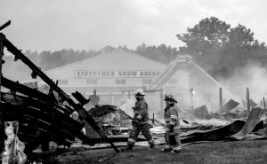 FIREFIGHTERS work to extinguish a fire that destroyed two buildings and damaged several others at the historic Fryeburg Fairgrounds Wednesday. AP PHOTO/BREWSTER BURNS