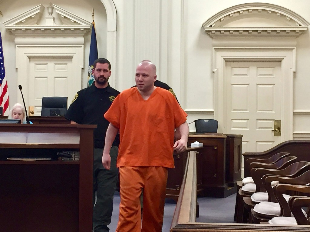 Derek Poulin is escorted into a courtroom at York County Superior Court in Alfred on Tuesday. He is seeking to have his life sentence reduced.