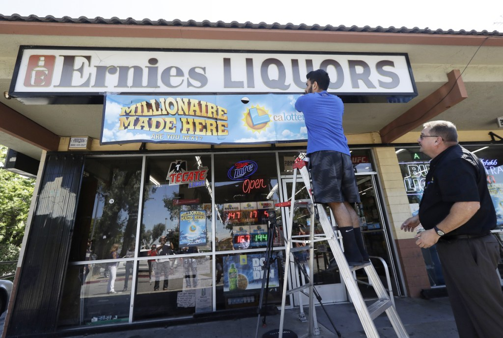 California Lottery official Mike Neis, right, watches as Amol Sachdev hangs a sign over his family's store Ernie's Liquors where a Mega Millions lottery ticket worth more than $500 million was sold in San Jose, Calif.