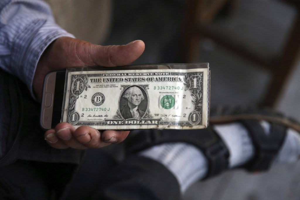An Iranian street money exchanger holds a U.S. banknote in downtown Tehran, Iran. As the Trump administration re-imposes sanctions on Iran that were lifted by the Obama administration under the nuclear deal, American allies fear greater regional instability. Sanctions on trade in Iranian metals and automobiles go back into effect Monday. The more significant sanctions — those on Iran's oil sector and central bank — go back into effect in November