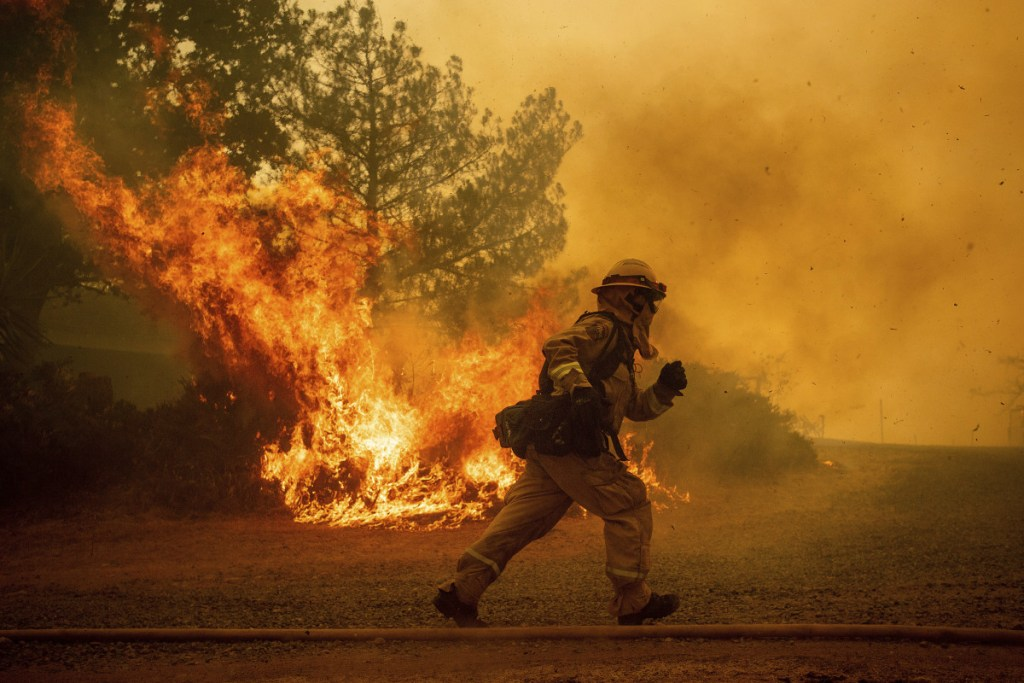 A firefighter runs while trying to save a home on July 31 as a wildfire tears through Lakeport, Calif. The residence eventually burned. Authorities say a rapidly expanding Northern California wildfire burning over an area the size of Los Angeles has become the state's largest blaze in recorded history. It's the second year in a row that California has recorded the state's largest wildfire.