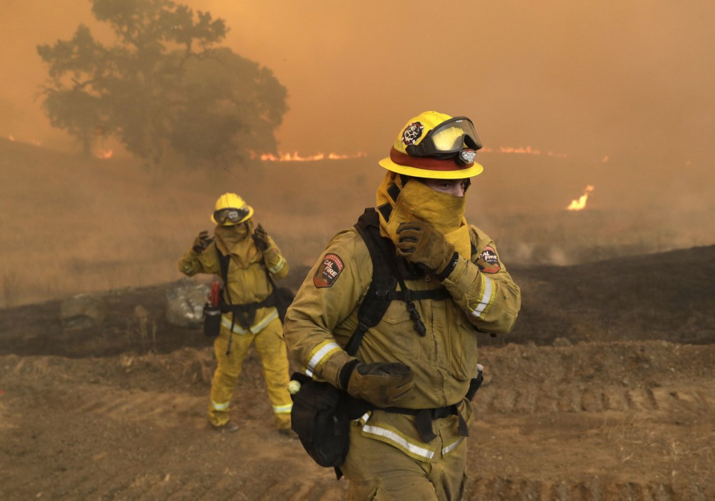 Firefighters with Cal Fire Mendocino Unit cover themselves to protect from smoke and ash created by an advancing wildfire Monday in Lakeport, Calif.