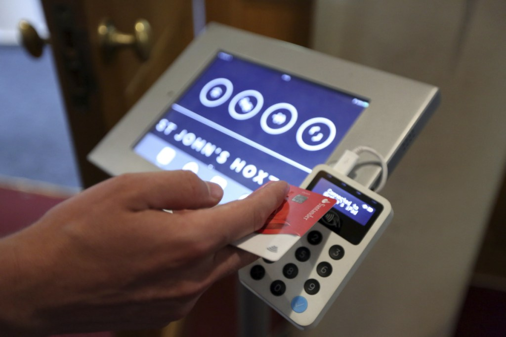 This card reader allows churchgoers to donate money at St. John's in London. Preset sums range from $6.50 to $65.50.