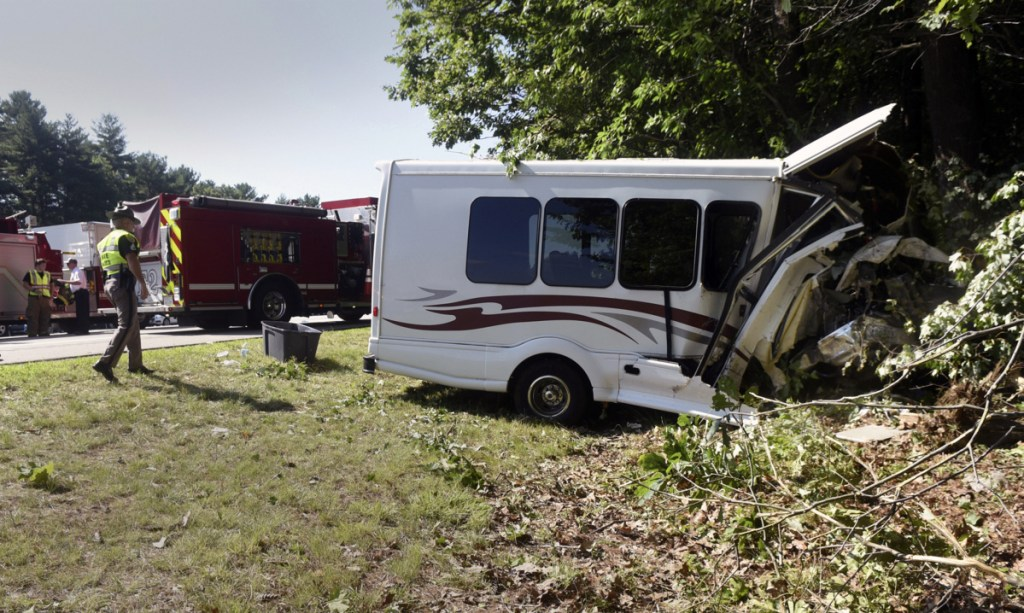New Hampshire State Police inspect a van involved in an accident Friday on Interstate 95 in Greenland, N.H. Children with a Kittery Recreation Department program were among those injured when the van crashed in a wooded area. One was taken to a Boston hospital with serious injuries.
