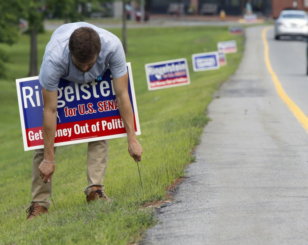 Sammy Potter, assistant to U.S. Senate candidate Zak Ringelstein, erects political signs Thursday along Franklin Street in Portland. Crystal Canney, a candidate for a state Senate seat, had the first signs posted along Franklin Street, prompting some complaints to City Hall.