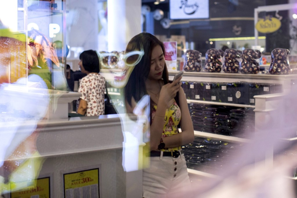 "A shopper looks at a smartphone at a mall in Bangkok, Thailand, in June. By 2020, more than half of the world's population will be ""middle class,"" one researcher says."