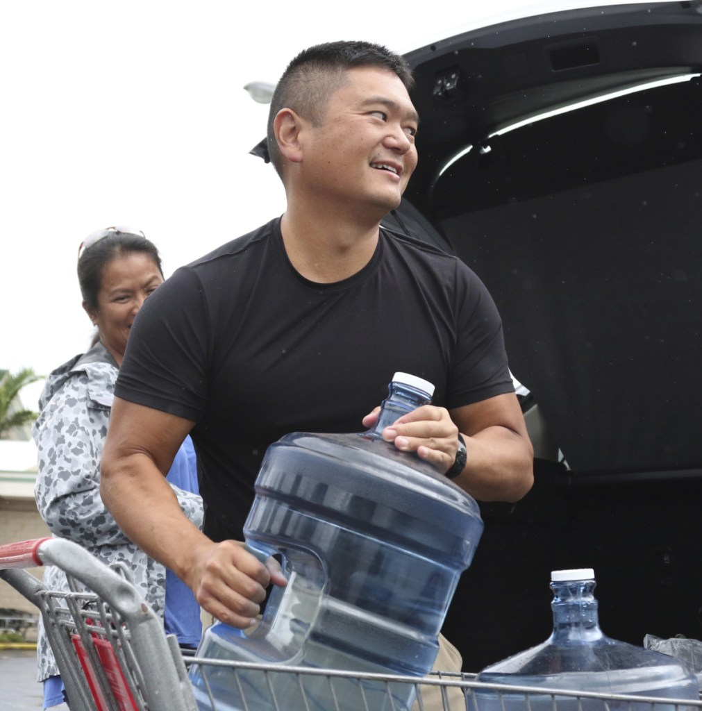 Loren Aquino of Honolulu loads water into his car on Wednesday.