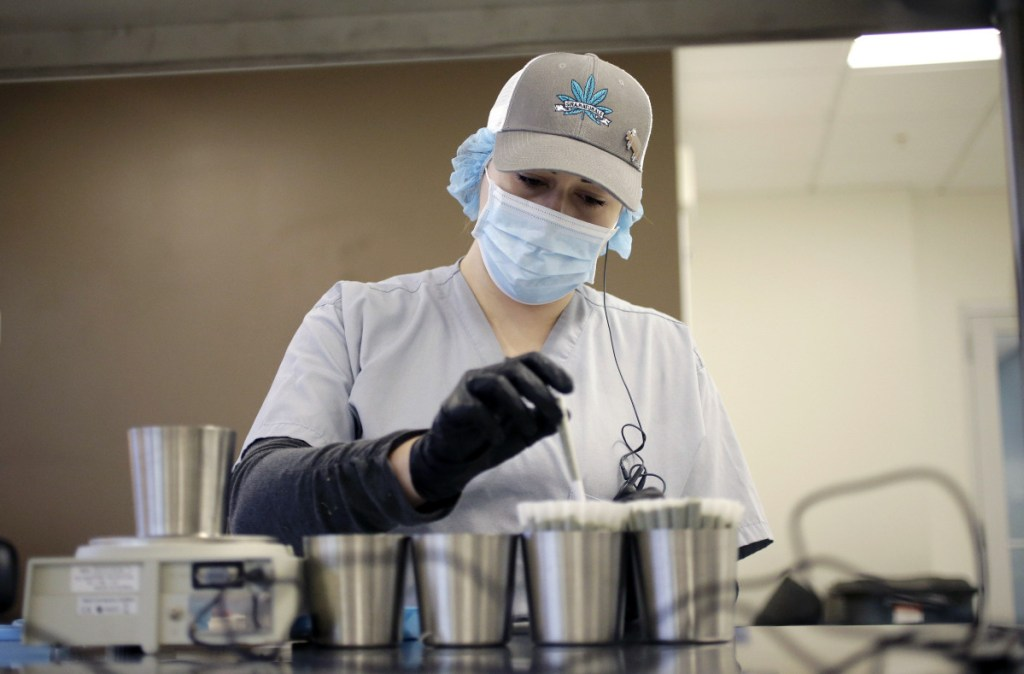 Emma Caron weighs and crowns medicinal cannabis cigarettes at Sira Naturals in Milford, Mass. Two Massachusetts labs have won approval to test marijuana for retail sales.