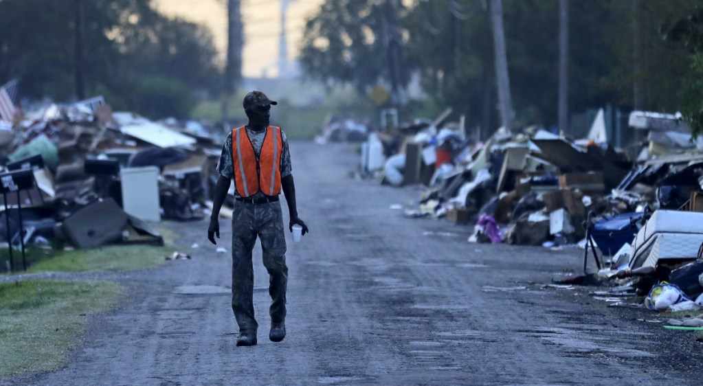 FILE - In this Sept. 28, 2017, file photo, a man walks past debris from homes on his street damaged in flooding from Hurricane Harvey as an oil refinery stands in the background in Port Arthur, Texas. Although many Texas families are still struggling to recover from Hurricane Harvey a year after it caused widespread damage and flooding along the Gulf Coast and in and around Houston, daily life has mostly returned to normal in many of the hardest hit communities. (AP Photo