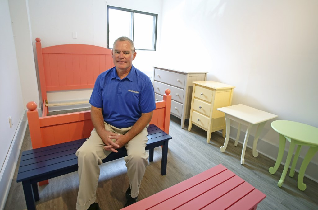 Dave Gallati, director of operations at Maine Woodworks, sits with some finished pieces. Maine Woodworks will open a showroom in Saco for the first time to showcase the pieces crafted by its integrated workforce.
