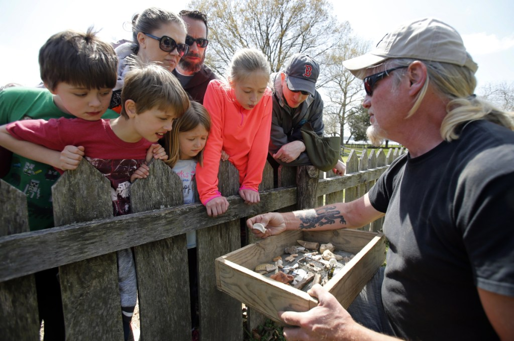 A Jamestown Rediscovery Foundation archeologist displays artifacts dating back to the 17th century when American slavery began in the historic Virginia community