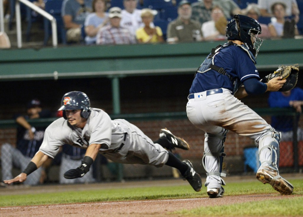 Jeremy Rivera dives past New Hampshire's catcher Max Pentecost to score a run in the first inning. Rivera went 3 for 5 with three runs scored, and the first three batters in the Sea Dogs lineup collected eight hits, five runs and five RBI.