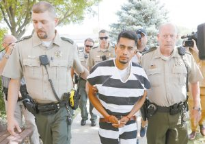 CRISTHIAN BAHENA RIVERA is escorted into the Poweshiek County Courthouse for his initial court appearance on Wednesday in Montezuma, Iowa. Rivera is charged with first-degree murder in the death of Mollie Tibbetts, who disappeared July 18 from Brooklyn, Iowa. AP PHOTO/CHARLIE NEIBERGAL
