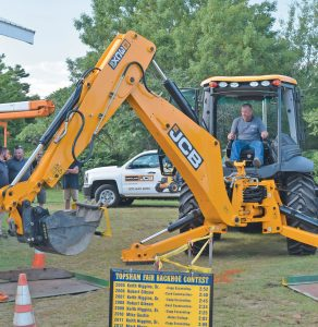 DAN BOWLEY of Bowley Excavating competes in the backhoe contest. The competition was part of the construction rodeo Thursday at the Topsham Fair. Competitors are timed as they move objects from one pad to another. Bowley had some experience, competing in his second backhoe event. Thursday was his first competition at the Topsham Fair. The fair continues throughout the weekend. CHRIS QUATTRUCCI/THE TIMES RECORD