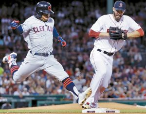 CLEVELAND INDIANS runner Francisco Lindor, left, outruns Boston Red Sox starting pitcher Rick Porcello, who was covering first, on a single during the sixth inning of a baseball game at Fenway Park in Boston on Monday. The Tribe beat the Red Sox, 5-4. THE ASSOCIATED PRESS