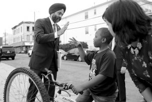 New Jersey Attorney General Gurbir Grewal, center, greets Jasim Jackson, 9, after a news conference announcing pollution lawsuits filed by the state, Aug. 1 in Newark, N.J. Grewal, is the nation's first Sikh state attorney general. AP PHOTO / JULIO CORTEZ