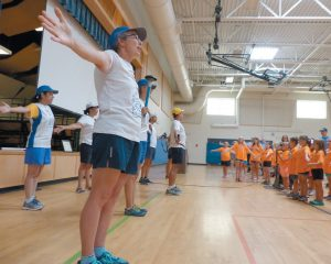 SARANYU PEARSON of Australia and her fellow U.S. peace runners, teacher Brunswick Parks and Recreation summer camp students the World Harmony Run Song Friday at Harriet Beecher Stowe Elementary School, in the photo on the left. Above, children attending the Brunswick Parks and Recreation Department's summer camp carry their own torches as they follow peace runner DARCIE MOORE / THE TIMES RECORD