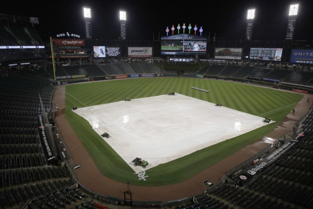 A tarp covers the infield as baseball fans wait out a rain delay during a baseball game between the Boston Red Sox and the Chicago White Sox on Friday night in Chicago. The delay lasted 2 hours and 9 minutes.