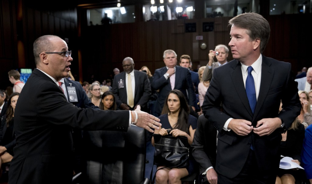 Fred Guttenberg, left, the father of a Parkland school shooting victim, attempts to shake hands with Supreme Court nominee Brett Kavanaugh as the Senate Judiciary Committee breaks for lunch Tuesday.