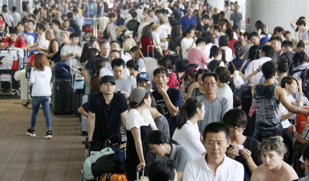 Passengers wait in lines Wednesday to board buses to take them from flood-stricken Kansai International Airport.