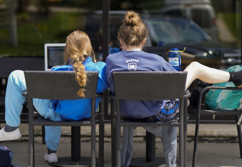Two customers relax outside a Starbucks store in Omaha, Neb. Researchers say it appears that neighborhoods chosen by Starbucks for new stores are often poised to see a jump in housing prices.