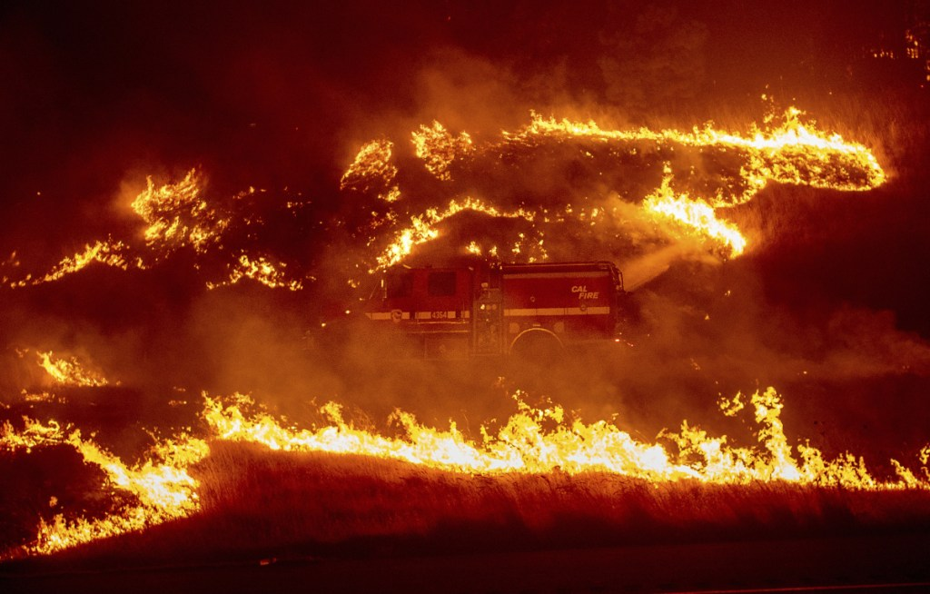 Flames from a backfire burn around a fire truck battling the Delta Fire in the Shasta-Trinity National Forest, Calif., on Thursday, Sept. 6, 2018.