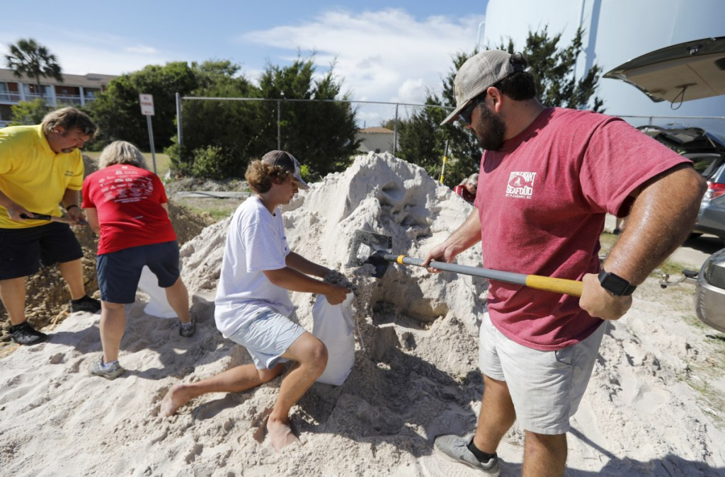 Walker Townsend, right, fills a sand bag while Dalton Trout, center, holds the bag at the Isle of Palms, S.C., municipal lot, where the city was giving away sand in preparation for Hurricane Florence.