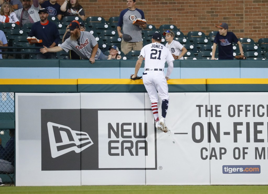 Tigers left fielder JaCoby Jones climbs the outfield wall but can't reach a two-run home run by the Astros' Tyler White in the fourth inning Tuesday in Detroit. Houston won, 5-4.
