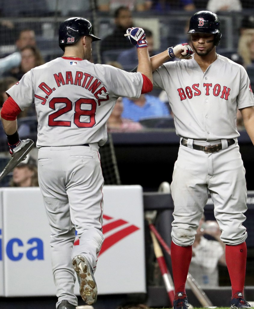 Boston's J.D. Martinez  bumps forearms with Xander Bogaerts after his sacrifice fly drove in Ian Kinsler in the third inning of Tuesday's 3-2 loss to the Yankees in New York.