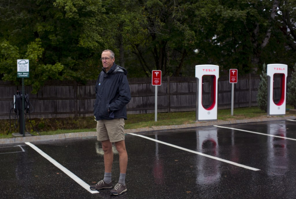 "Bill Yeo, L.L. Bean Outdoor Discovery School's retail manager, poses for a portrait in front of the store's new electric car charging stations. Yeo said if electric vehicles take off he ""hopes the whole parking lot will someday be an EV charging station."""