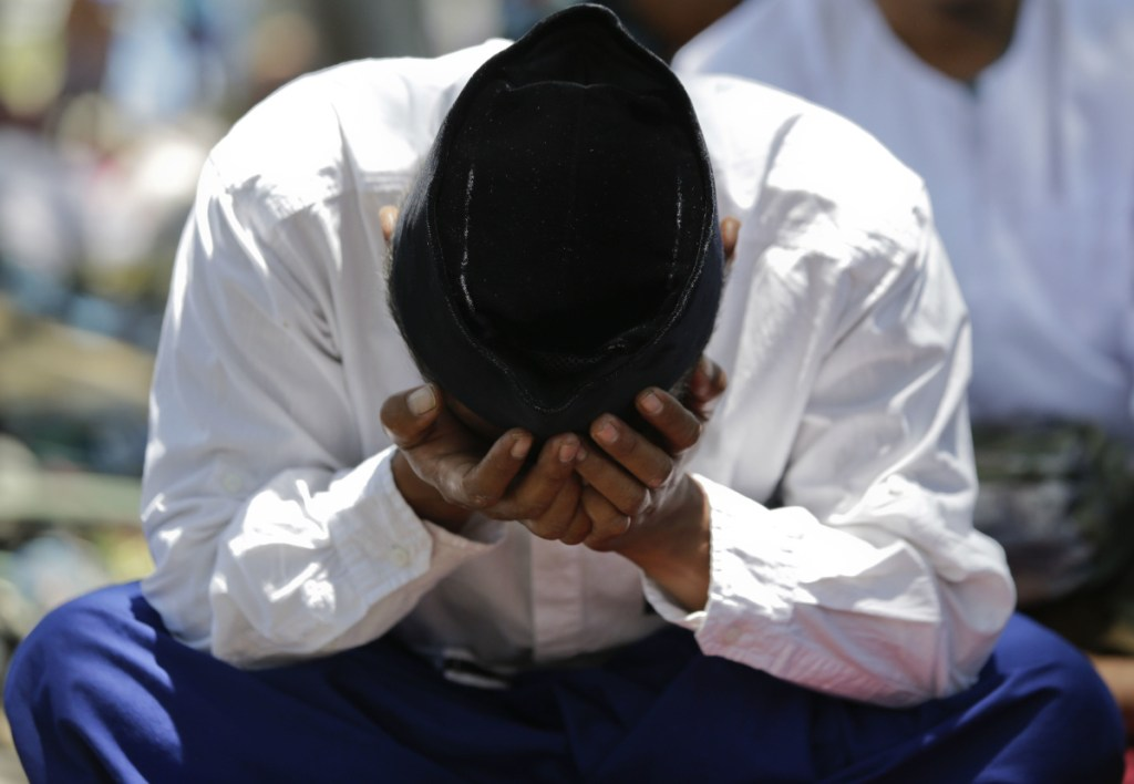 A man cries during Friday prayers outside a mosque damaged by an earthquake and tsunami in Palu on the Indonesian island of Sulawesi.