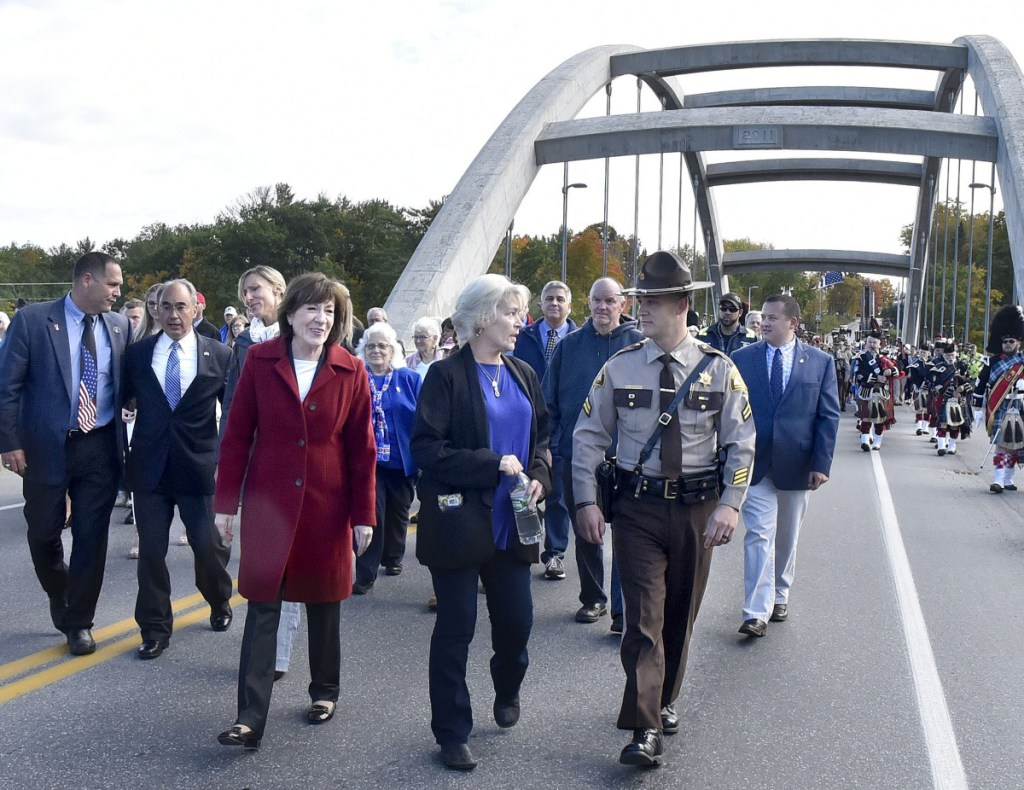 Sheryl Cole, center, walks with Sen. Susan Collins and her son, Somerset County Sheriff's Deputy David Cole, as they and hundreds of others cross the newly dedicated Cpl. Eugene Cole Memorial Bridge, named in honor of her husband, in Norridgewock on Sunday. Walking at left of Collins is U.S. Rep. Bruce Poliquin.