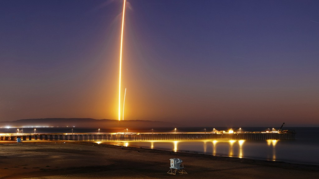 Two streaks in this long-exposure photo show a SpaceX Falcon 9 rocket lifting off, left, from Vandenberg Air Force Base as seen from Pismo Beach, Calif., on Sunday, and then its first stage returning, right, to Earth at a nearby landing pad.