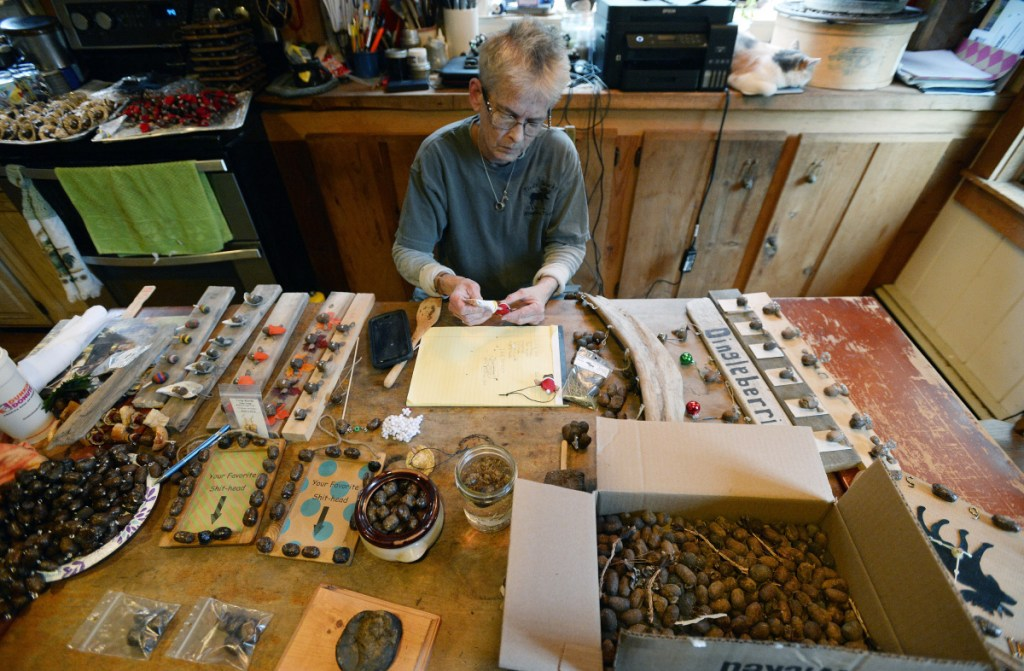 """Mary Winchenbach makes moose turd art in her kitchen. She recently quit her job to keep up with orders. """"When you put them eyeballs on them turds, they get their own little personalities, God bless them,"""" she said."""